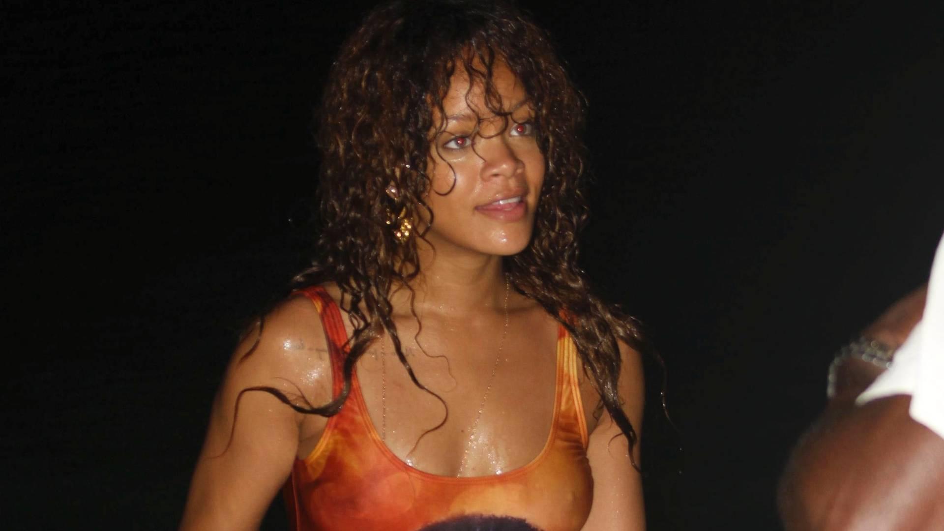 Com um maiô que tem o rosto de Bob Marley estampado, Rihanna curte praia em noite de verão em Barbados (6/8/11)
