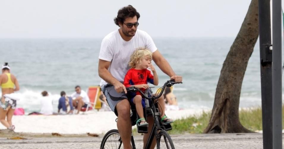 Thiago Lacerda passeia de bicicleta com o filho pela orla da Barra da Tijuca (14/8/11)