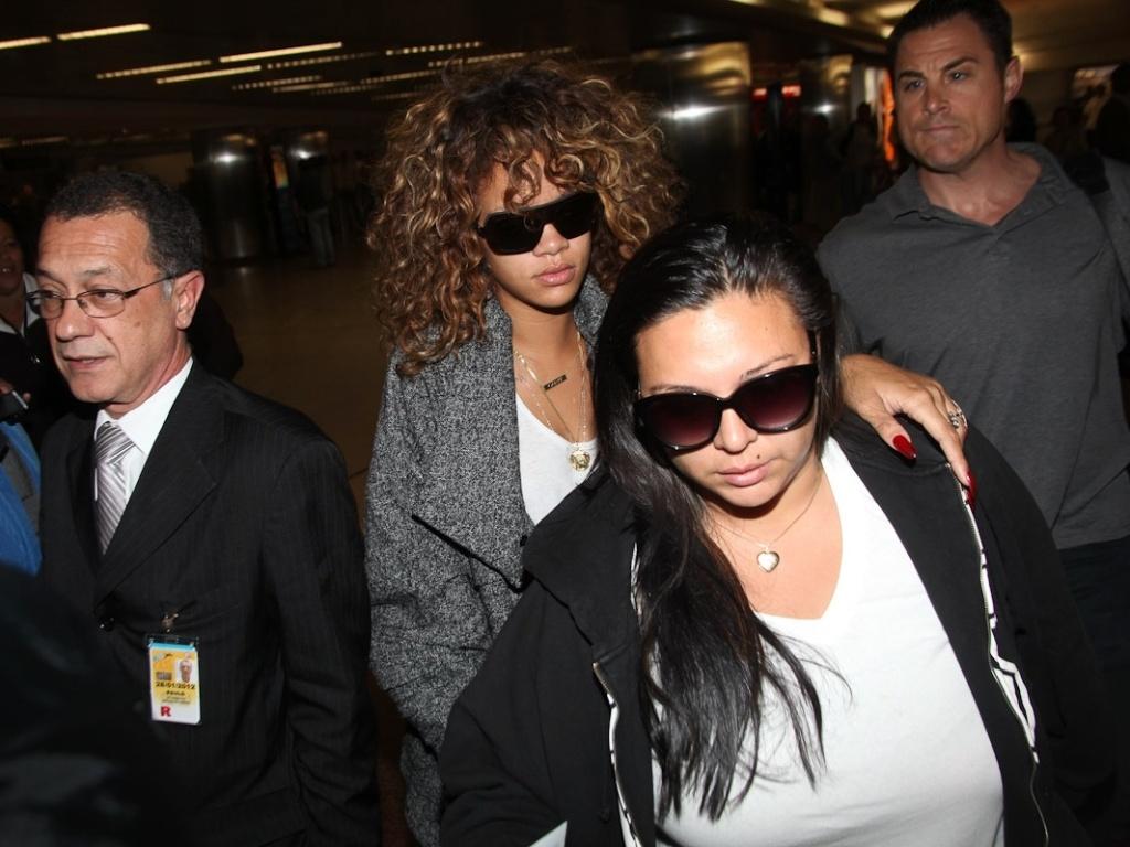 A cantora Rihanna (de casaco cinza) desembarca no aeroporto de Guarulhos (16/9/2011)