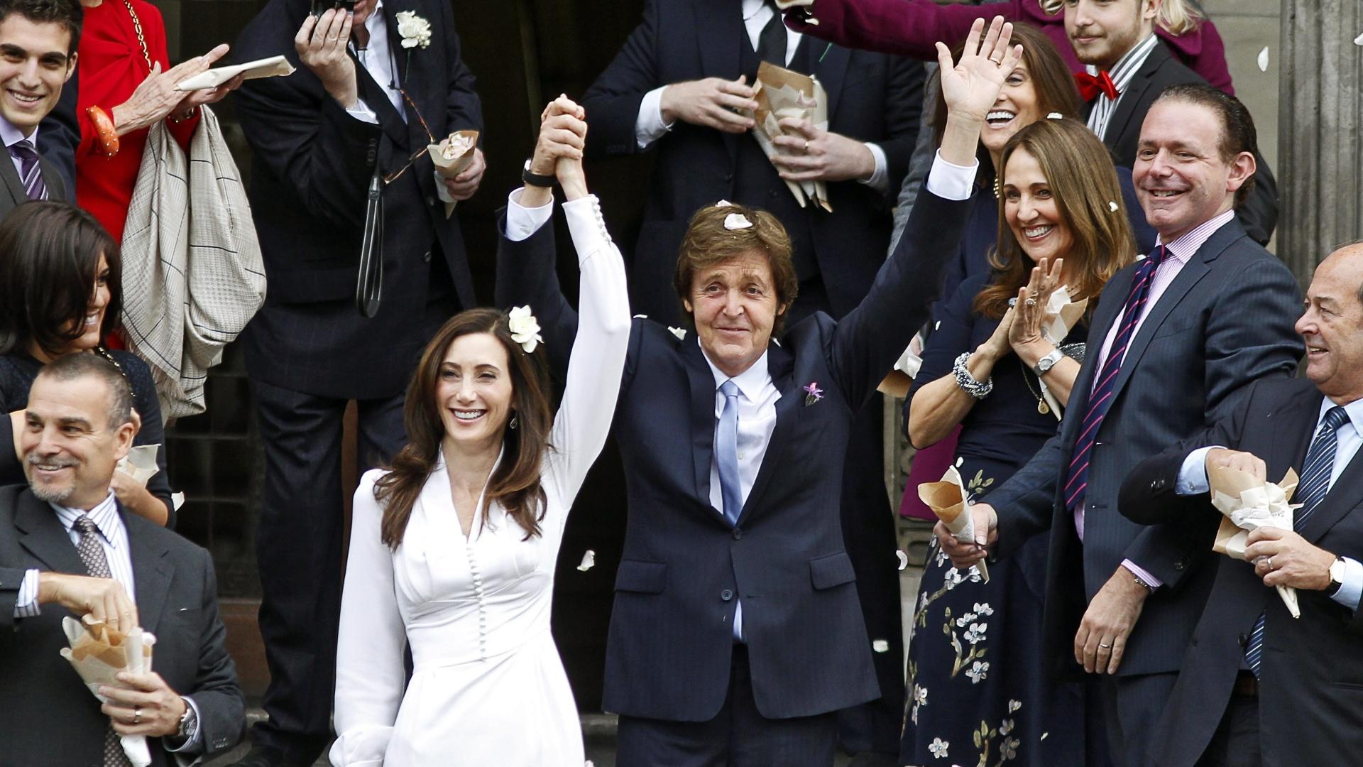 Paul McCartney e Nancy Shevell acenam para os presentes ao deixarem cartório em Londres (9/10/2011)