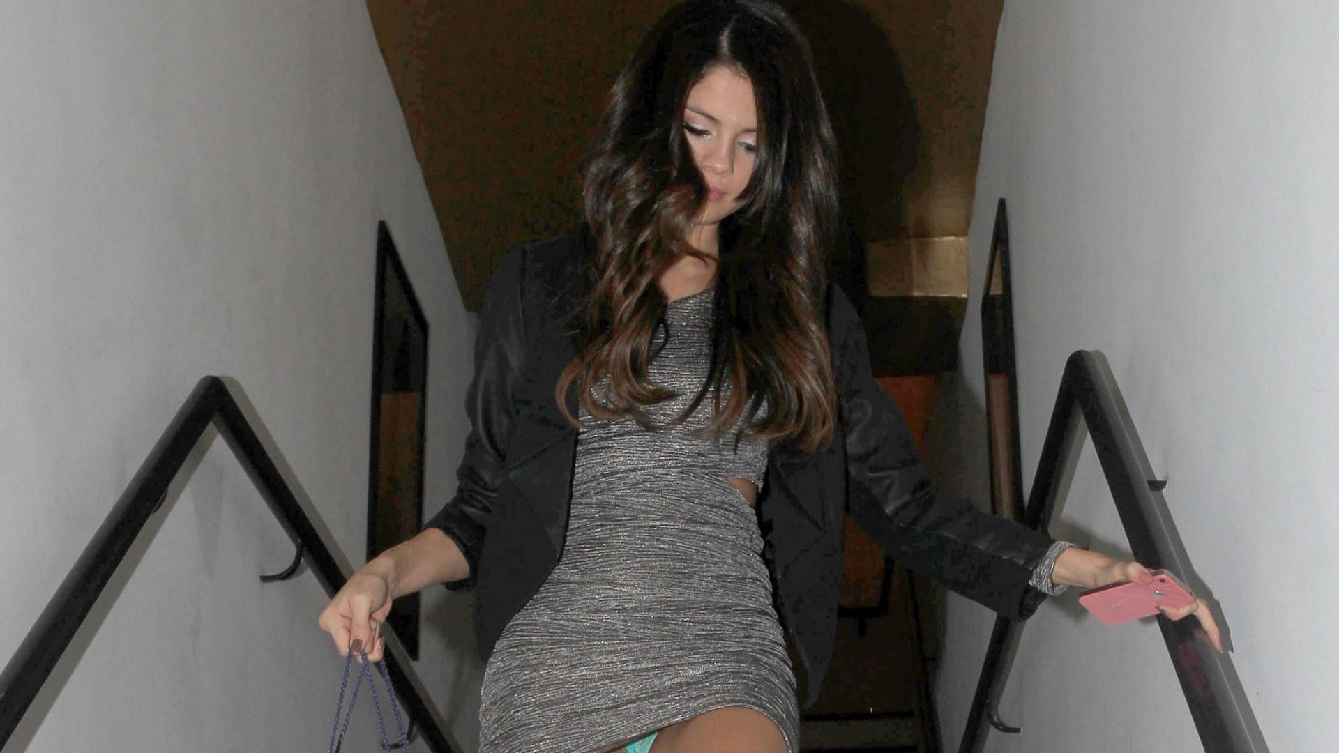 Com vestido curto, Selena Gomez deixa calcinha aparecer ao descer escada (03/11/2011)