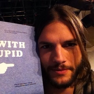 Após polêmica no Twitter, Ashton Kutcher publica imagem ao lado de cartaz com os dizeres