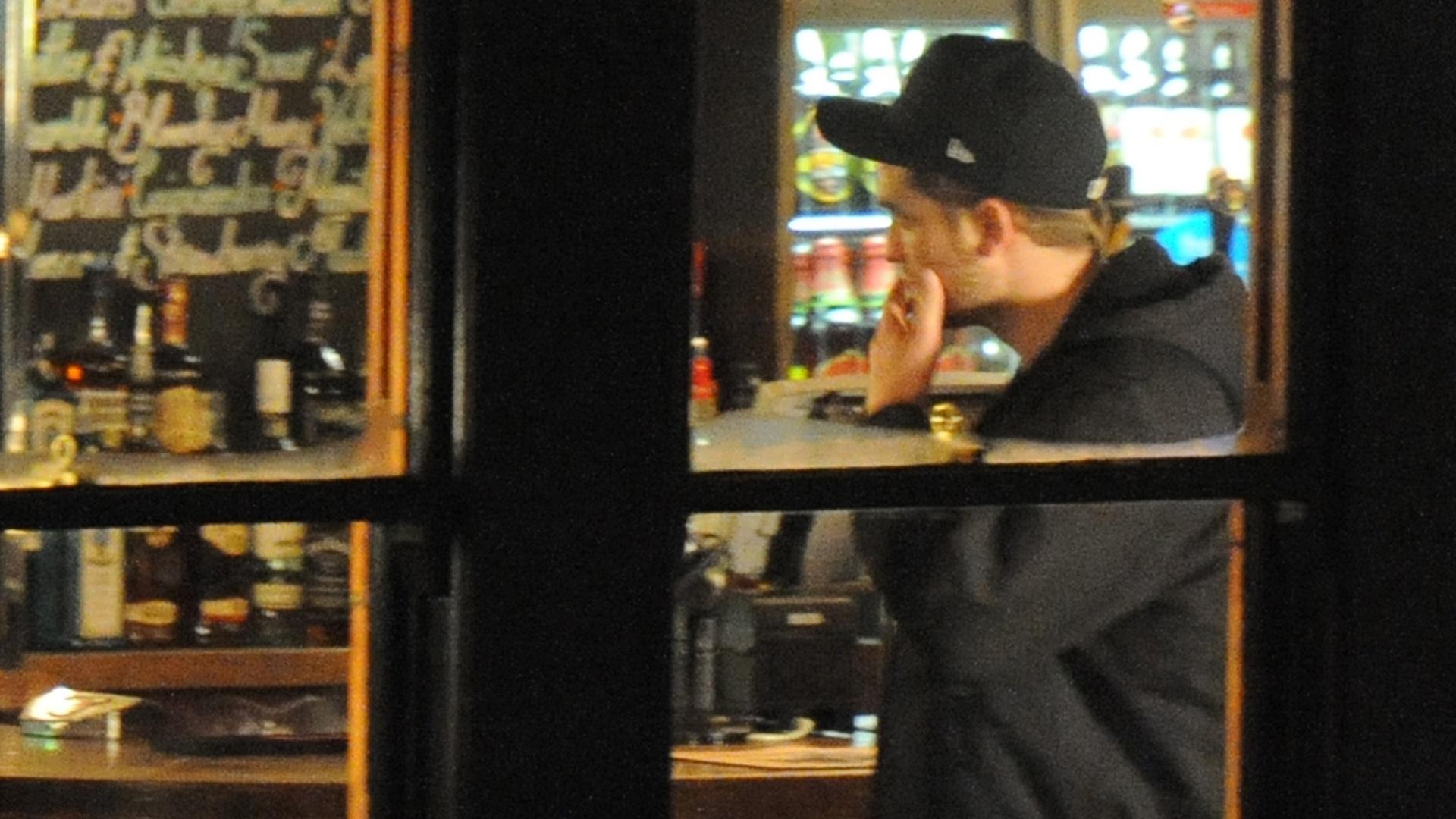 Robert Pattinson se diverte tomando umas e outras ao lado de amigos e da namorada, Kristen Stewart, num bar de Camden Town, bairro de Londres (23/11/11).