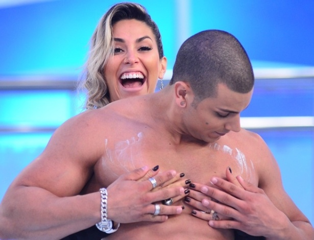 Dani Bolina passa creme no corpo de modelo em programa de auditório (02/12/2011)