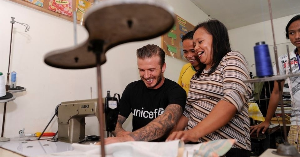 David Beckham visita abrigo de crianças carentes na Filipinas e mostra seus dotes no corte e costura (2/12/11)