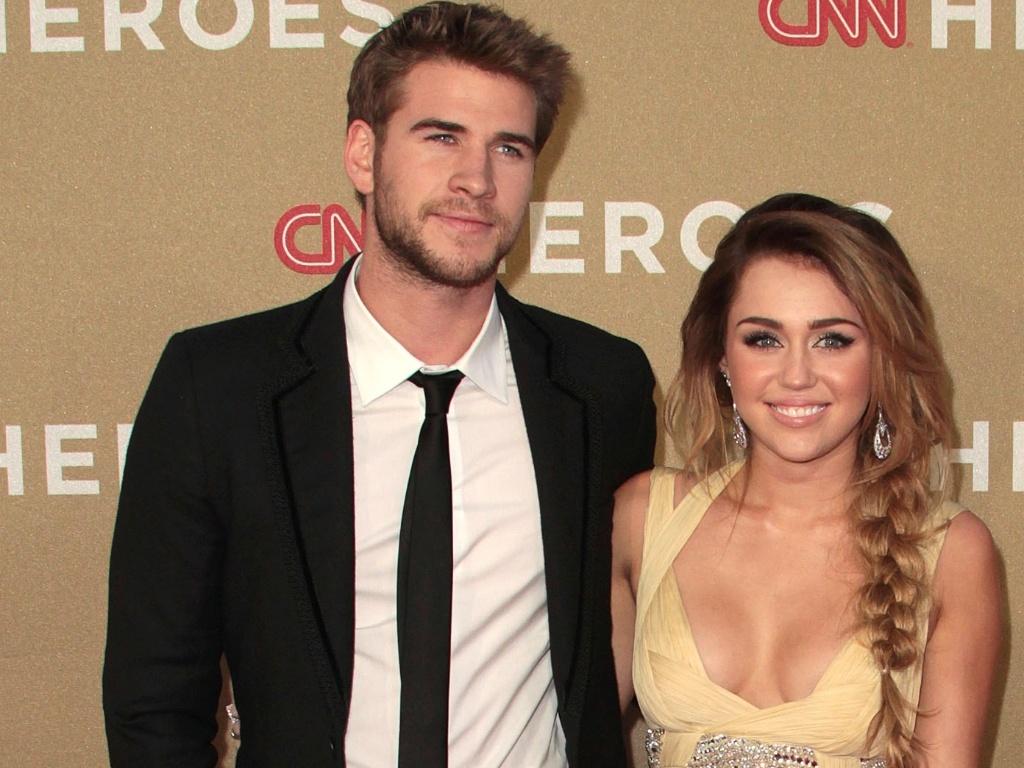 Com vestido bem decotado, Miley Cyrus e o namorado, Liam Hermsworth, vão à evento de TV (11/12/11)