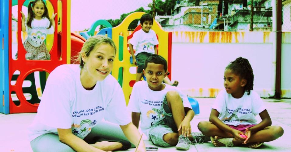 A atriz Luana Piovani posa com crianças para ensaio
