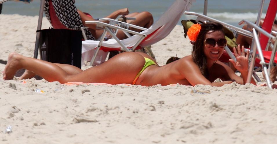 A ex-panicat Nicole Bahls acena para paparazzo enquanto toma sol na praia da Barra da Tijuca, na zona oeste do Rio de Janeiro (15/2/12)