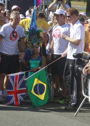 Com uma bandeira do Brasil nas m&#227;os, Harry prepara-se para dar a largada da corrida beneficente (10/3/12)