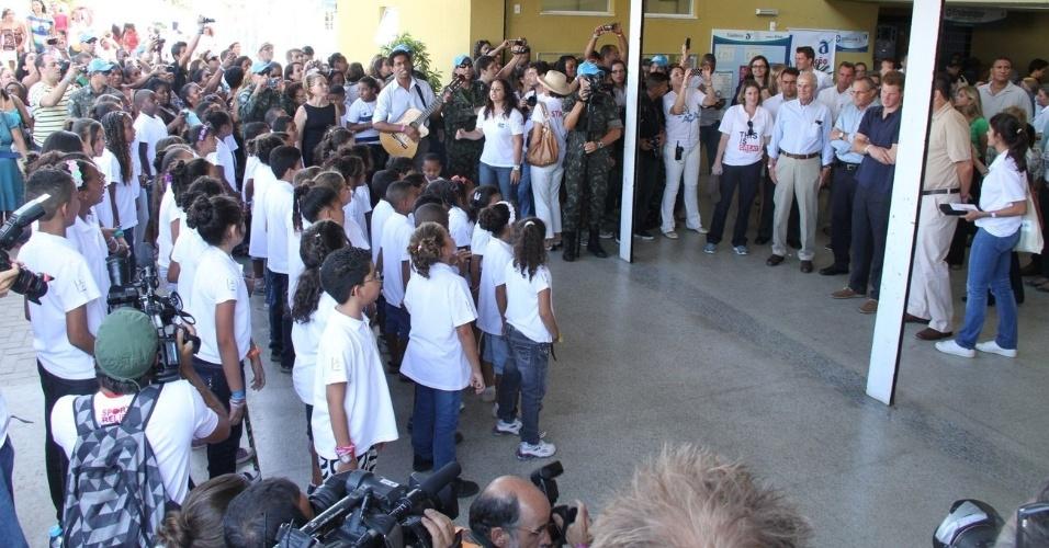 O príncipe Harry chega ao Complexo do Alemão, onde é recebido por um coral formado por crianças da comunidade, no Rio de janeiro (10/3/12)