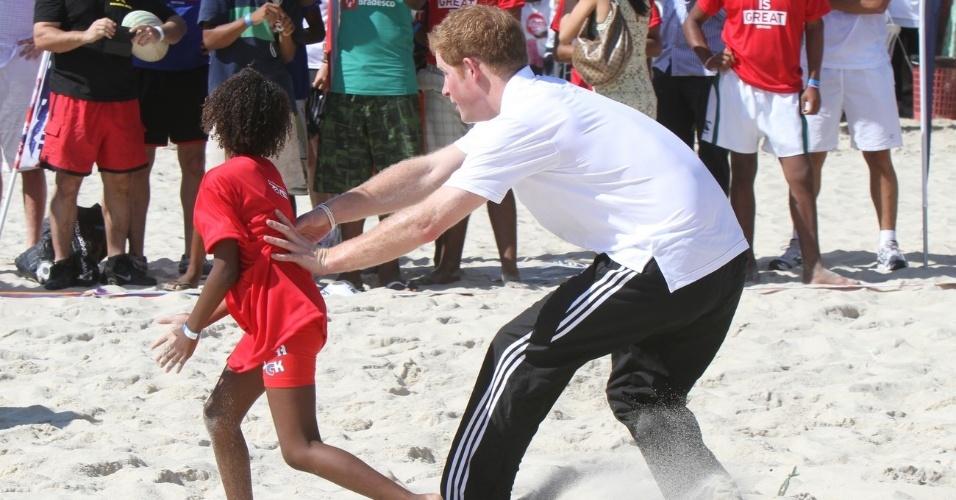 O príncipe Harry joga rúgbi com crianças do Morro do Cantagalo, na Zona Sul carioca, no Aterro do Flamengo (10/3/12)