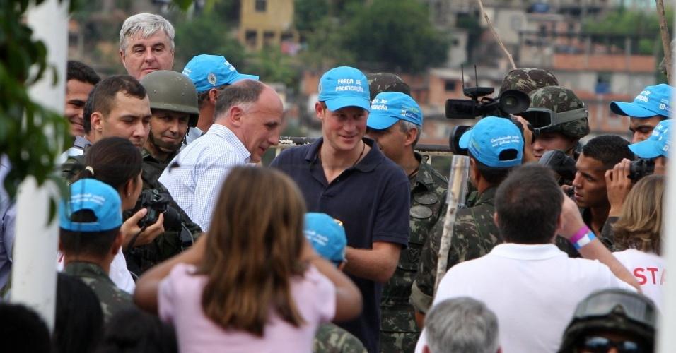 Príncipe Harry coloca boné da força de pacificação no Complexo do Alemão, no Rio de Janeiro (10/3/12)