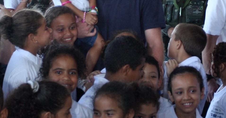 Príncipe Harry posa para fotos com crianças no Complexo do Alemão, no Rio de Janeiro (10/3/12)