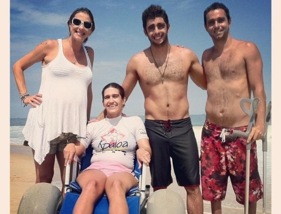 """Luana Piovani posta uma foto sua no Twitter com amigos do marido Pedro Scoby que fazem parte de um projeto que leva deficientes físicos para aprenderem a surfar, no Rio de Janeiro. A atriz comentou a ação dos rapazes: """"eu sou feliz pq conheço e aprendo com pessoas do bem<3"""" (11/3/12)"""