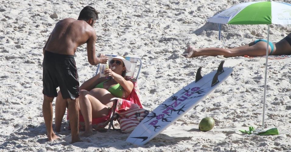Grávida de nove meses de seu primeiro filho, Dom, Luana Piovani e o marido, o surfista Pedro Scooby, aproveitaram o dia de sol na Prainha, na Barra da Tijuca. A atriz se deliciou com biscoitos