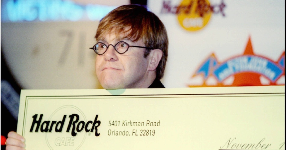 O cantor Elton John recebe cheque donativo para sua Fundação contra a AIDS: Rock star Elton John poses for photographers with a check from the Hard Rock Cafe, November 16 in New York. John was given the check for over $500,000 from the sale of t-shirts for the Elton John AIDS Foundation. Photo by Jeff Christensen REUTERS