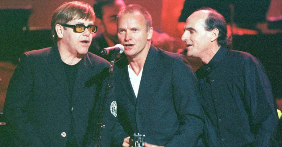 Os cantores Elton John [esq.], Sting e James Taylor [dir.] durante o show Rainforest Benefit em Nova York: Pop singers Elton John [L], Sting and James Taylor [R] sing together during the ninth annual Rainforest Benefit Concert in New York's Carnegie Hall, April 27. Proceeds from the concert are used to protect rainforest environments around the world. jc/Photo by Jeff Christensen REUTERS