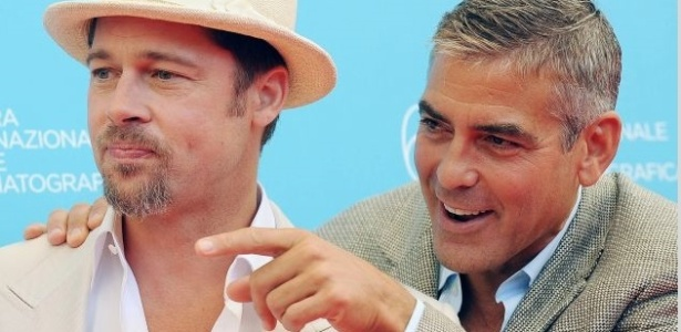 Brad Pitt e George Clooney com camisas e blazeres em tons claros em dia ensolarado