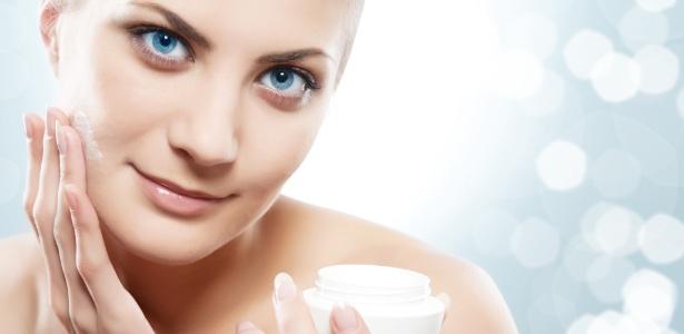 Mulher aplica hidratante facial em creme