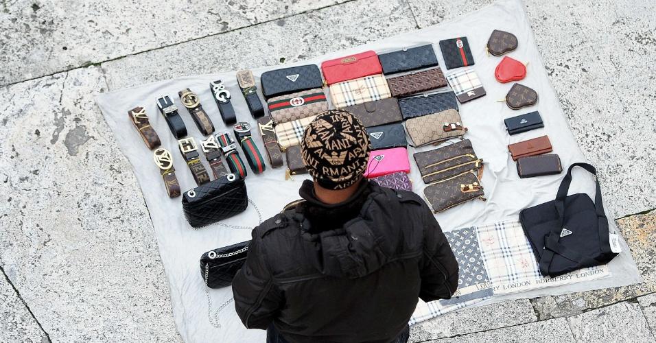 Camelô internacional: Vendedor ambulante exibe peças falsas da Burberry, Louis Vuitton e Prada na escadaria da praça Spagna, em Roma, Itália. Elas são expostas sobre um pano branco, para facilitar o recolhimento no caso de batidas policiais (4/1/2012)