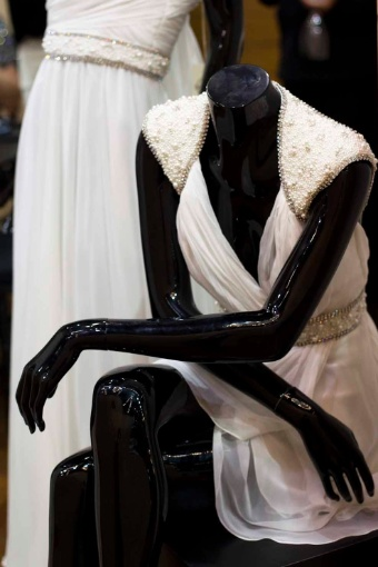 A Trinitá Couture tem vestidos sob medida e peças para pronta entrega. Os modelos da foto são feitos de musseline de seda pura com detalhes bordados de pérolas e aplicações de cristais Swarovski; R$ 5 mil, no manequim em pé, e R$ 4 mil, no manequim sentado