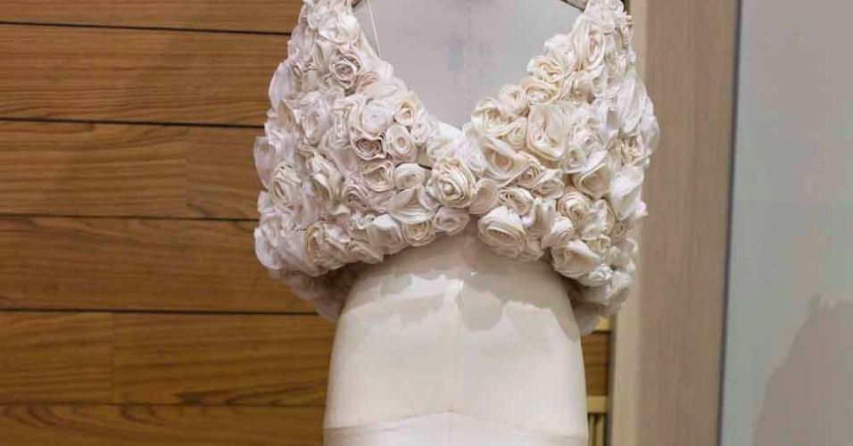 O modelo com faixas diagonais de seda pura e saia armada de gazar é um hit do ateliê de Bibi Barcellos e custa R$ 18 mil. A estola, que tem 360 flores de seda feitas à mão, sai por R$ 20 mil