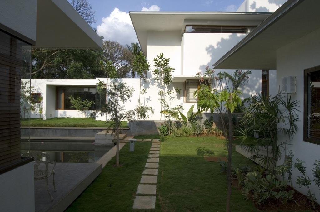 Um exterior de linhas horizontais suaves e longilineas, fechamentos de vidro e fachadas pintadas de branco envelopam a casa organizada por entre a natureza existente. Localizada em Bangalore, a residência foi projetada de acordo com a mandla Vastu Purusha, a antiga ciência indiana de orientação para edificações