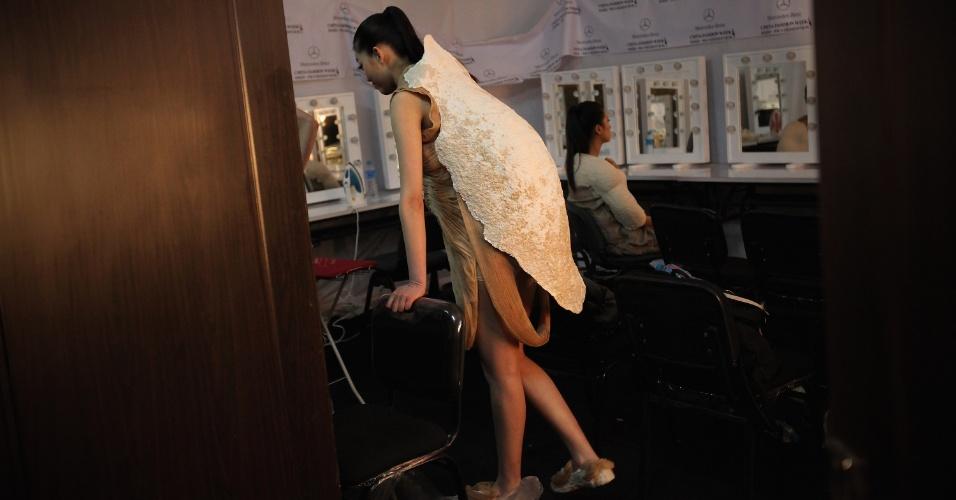 Modelo usa um vestido em forma de casulo no camarim do desfile de formatura da faculdade de artes da China, em Pequim (01/04/2012)