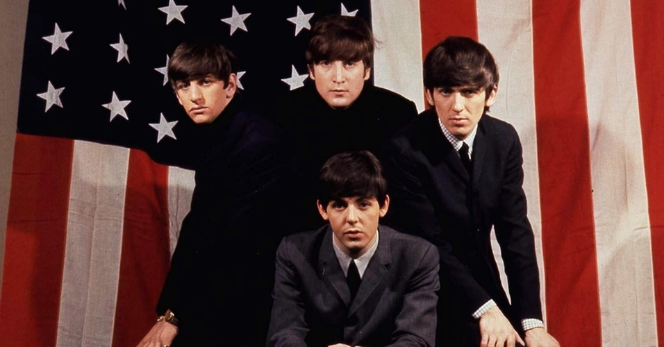 Os integrantes do Beatles Ringo Starr, John Lennon, George Harrison e Paul McCartney posam para foto em frente à bandeira dos Estados Unidos