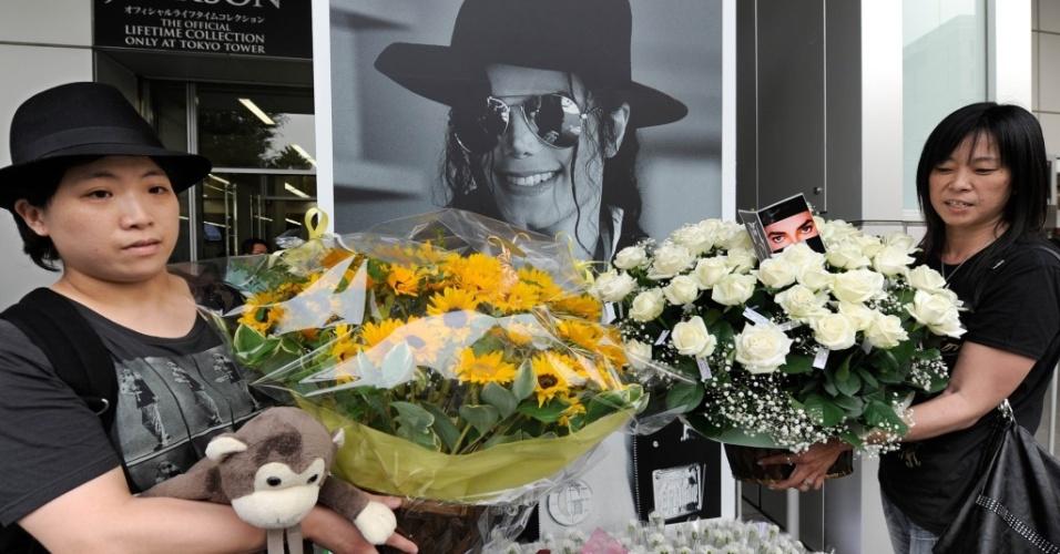 Fãs seguram flores em frente a cartaz com imagem de Michael Jackson em Tóquio (25/06/2010)