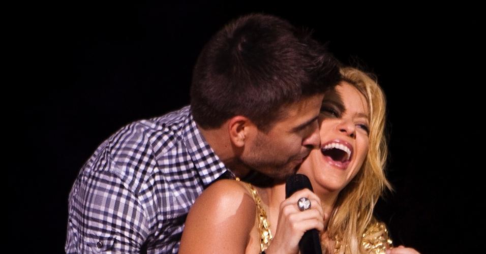 Shakira sorri ao ser abraça por seu namorado, o jogador de futebol Gerard Piqué, durante show em Barcelona, na Espanha (29/05/2011)