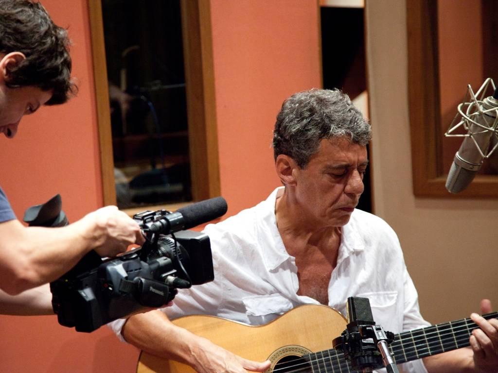 Chico Buarque toca violão e canta durante gravação do disco