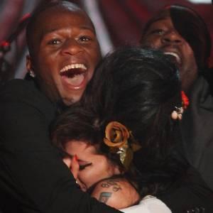 Amy Winehouse � abra�ada pelo m�sico Zalon na cerim�nia do Grammy, em Londres (10/02/2008)