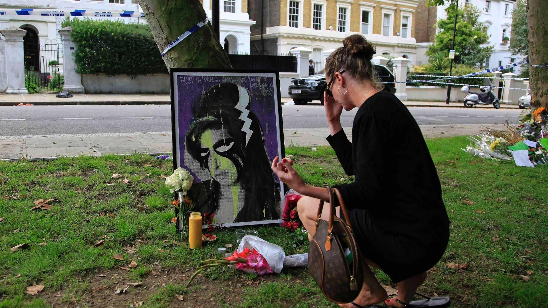 Mulher chora frente à pintura de Amy Winehouse que foi colocada próximo à casa onde a cantora morava em Camden, em Londres (24/07/2011)