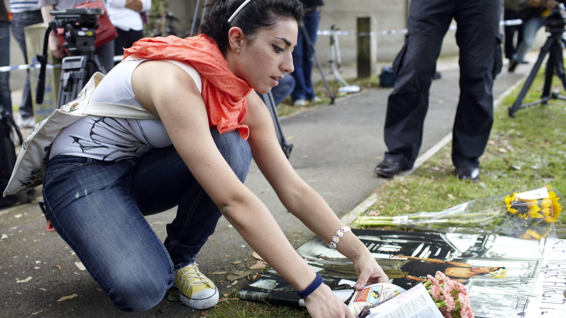 Mulher deixa flores ao lado de um pôster de Amy Winehouse, em frente à casa onde a cantora morava em Camden, em Londres (24/07/2011)
