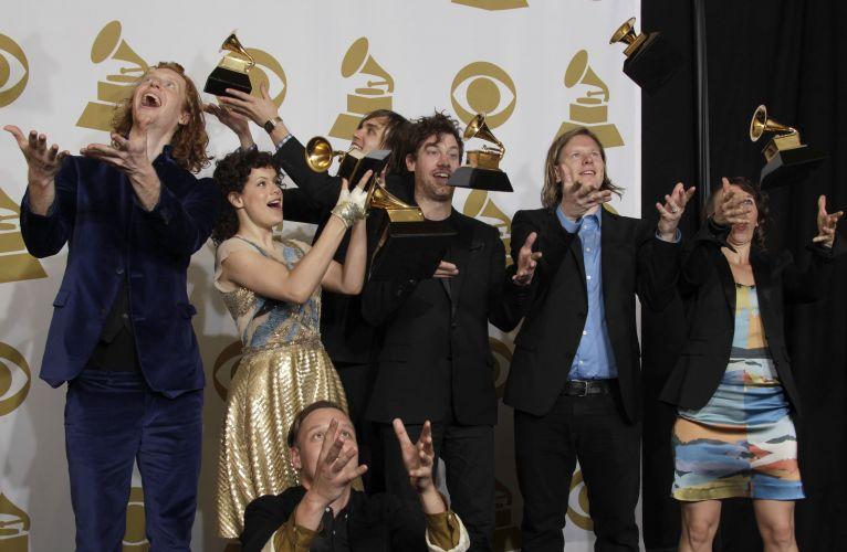 Os integrantes do Arcade Fire jogam seus troféus de melhor disco do ano para cima nos bastidores do Grammy, em Los Angeles (13/02/2011)