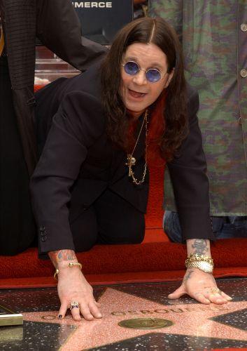 Ozzy Osbourne ajoelha em frente à homenagem que recebeu na calçada da fama em Hollywood, nos Estados Unidos (12/04/2002)
