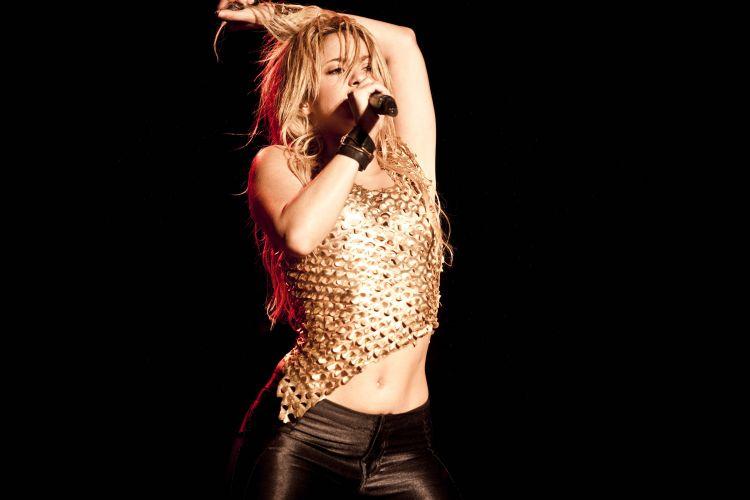 Com vestido dourado e calça escura justa, a cantora colombiana Shakira se apresenta na capital paulista como parte do evento Pop Music Festival (19/03/2011)