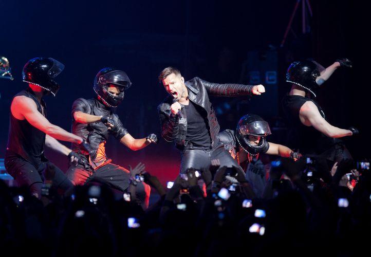 Com bailarinos usando capacetes, o cantor porto-riquenho Ricky Martin entoa versos de