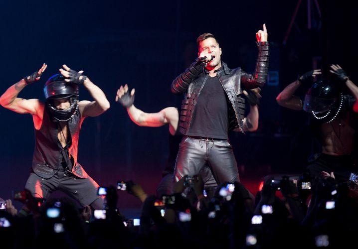 Com bailarinos usando capacetes, o cantor porto-riquenho Ricky Martin canta