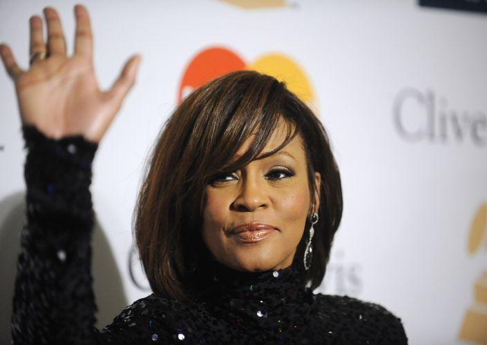 A cantora acena para fotógrafos durante a festa pré-Grammy