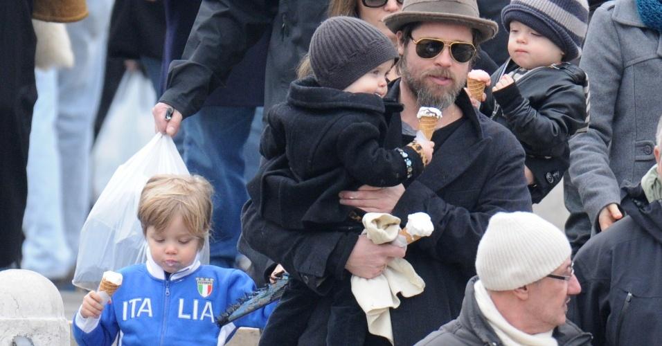 Angelina Jolie e Brad Pitt levam os filhos Shiloh (esq.), Vivienne (no colo de Pitt) e Knox (no colo de Jolie) para comprar um autêntico sorvete italiano em Veneza, na Itália, onde a atriz está gravando o filme