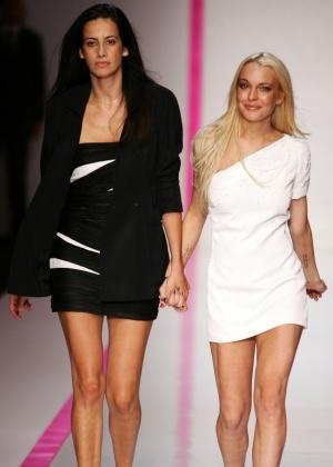 A atriz Lindsay Lohan (dir.) e a estilista da Ungaro Estrella Archs (esq.) entram na passarela após o desfile da marca na Semana de Moda de Paris (4/10/2009)