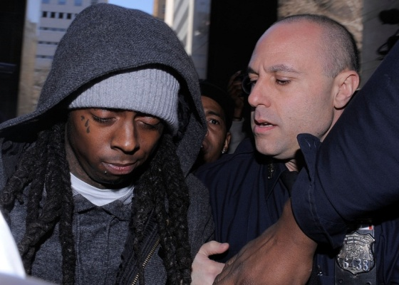 O rapper Lil Wayne (esq.) é cercado por policiais na entrada de tribunal de Nova York no dia em que foi condenado (8/3/2010)