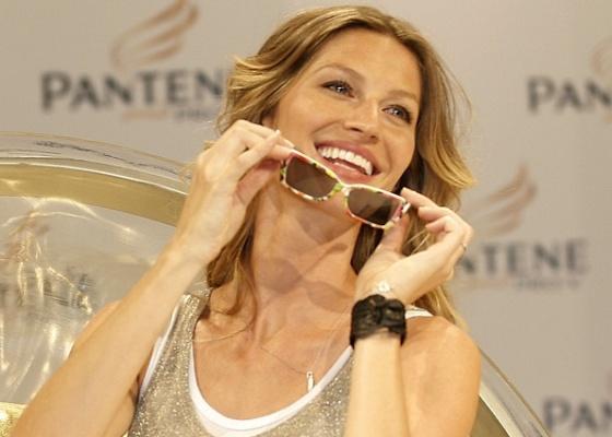 A top Gisele Bündchen brinca, durante evento de marca de produtos para o cabelo em SP, com óculos que ganhou de presente do