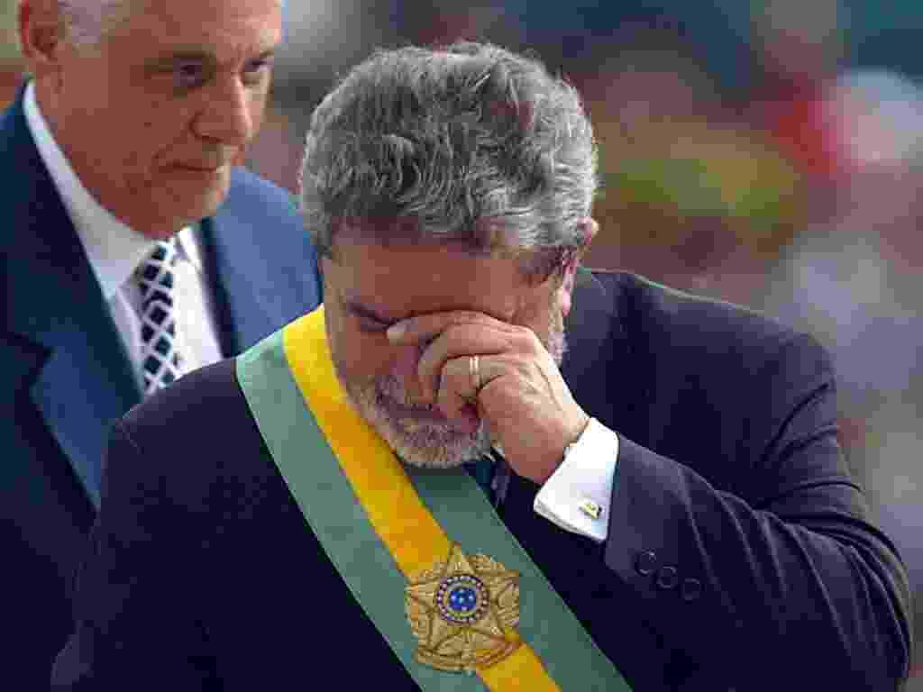 Lula se emociona após receber a faixa presidencial de Fernando Henrique Cardoso (ao fundo), em sua primeira posse, em Brasília (1/1/2003) - AFP