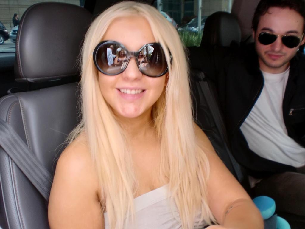 Ao lado do namorado, Matthew Rutler, Christina Aguilera sorri para fãs e fotógrafos que a aguardavam do lado de fora de seu hotel em São Paulo (1/2/2011)