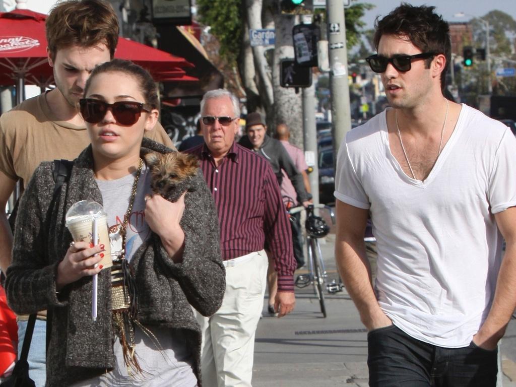 A cantora Miley Cyrus passeia com seu cão por Toluka Lake, na Califórnia, e encontra com seu suposto novo namorado, o ator Joshua Bowman (dir. de branco) (8/2/2011)