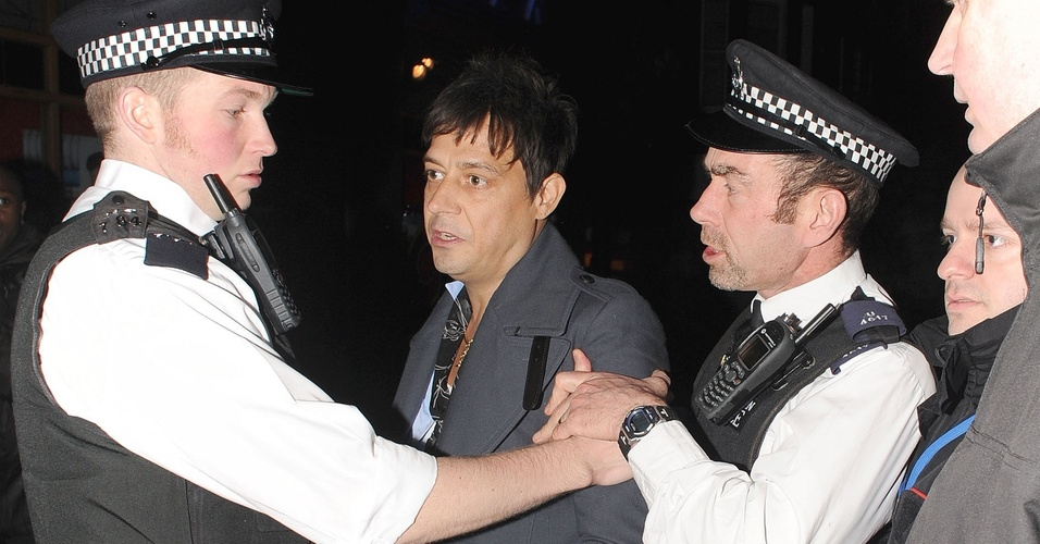 21.fev.2011: Jaime Hince, noivo de Kate Moss, é contido por policiais após discutir com paparazzi na saída de um clube noturno em Londres