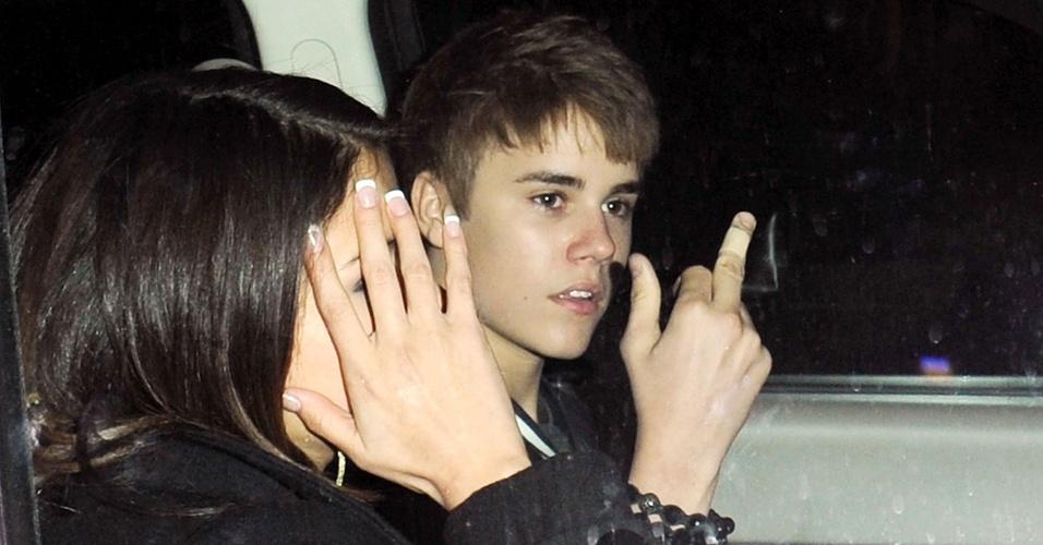 Justin Bieber mostra o dedo médio ao lado da atriz Selena Gomez, que esconde o rosto, na saída do aniversário do cantor, em Los Angeles (1/3/2011)